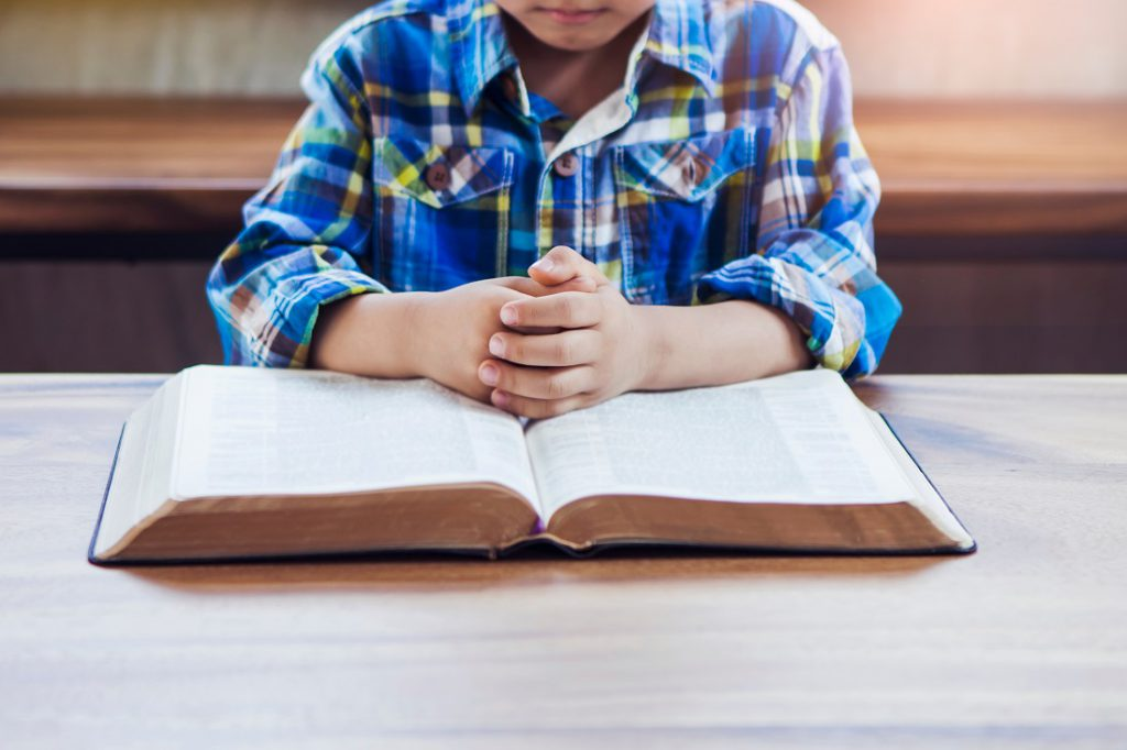 little boy in a blue flannel shirt with hands folded praying on an open Bible on a tabletop