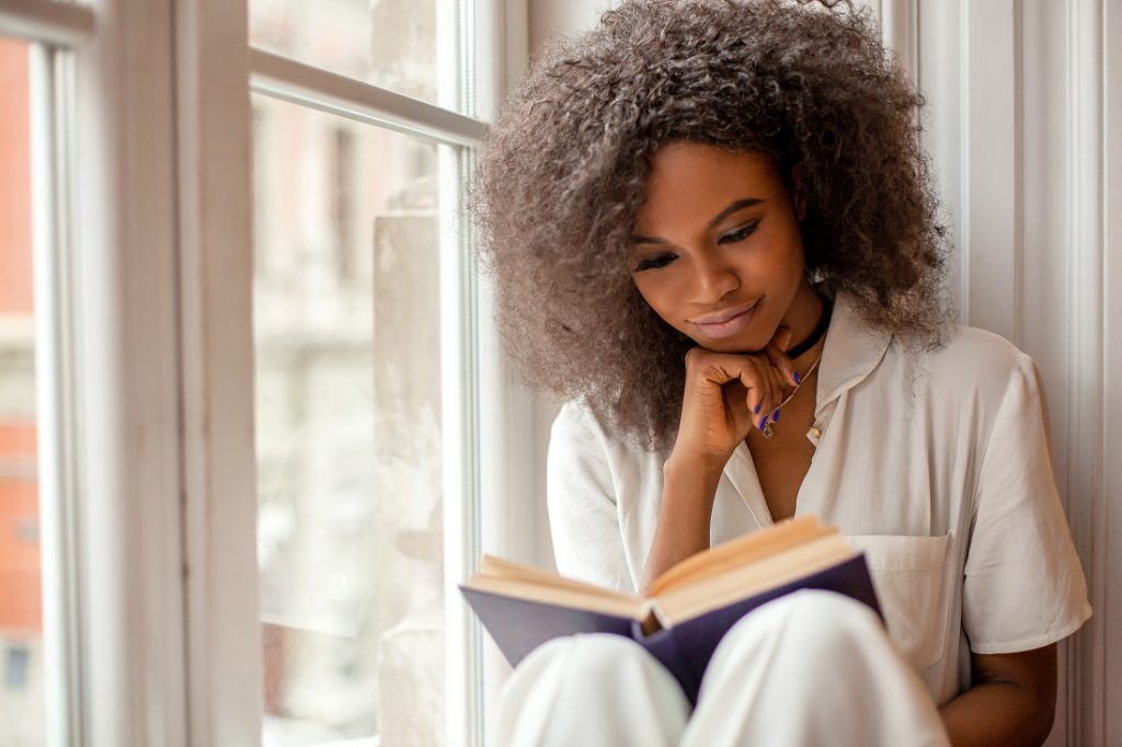 Pretty young black woman with thoughtful expression sitting on windowsill reading book.